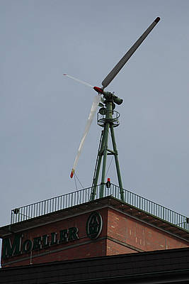 Typical of rooftop turbines, the rotor is tied down on this non-operating turbine in Holzhausen, Rheinland-Pfalz, 2005. The turbine is noteworthy in its own right. The turbine is probably an Allgaier built in the years from 1950-1959. It appears to be a twin to a turbine atop the same company's building, Klöckner-Moeller, alongside the main north-south line from Bonn to Koblenz. The Allgaier was a derivative of the work by the father of German wind energy, Ulrich Hütter, and was built by a small company in the south of Germany in Göppingen (near Uhingen). Altogether, there were about 200 units built and ranged in size from 6-10 kW. A photograph similar to this and this background information is contained in Windgeshichter by Jan Oelker, 2005.
